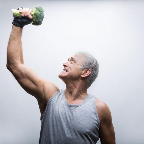 Senior man looking up and lifting broccoli