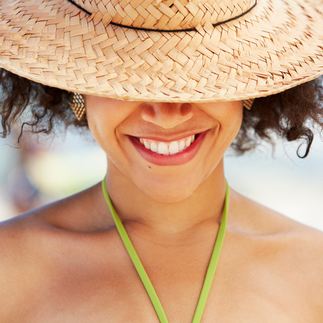 woman of color wearing sun hat over eyes while smiling