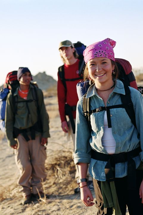Teenage girl (16-18) wearing backpack in desert with friends, portrait