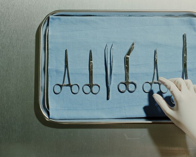 gloved hand reaches for medical scissors on a metal tray