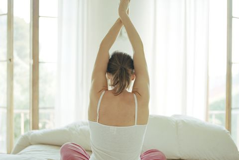 Woman sitting in bed, stretching, rear view