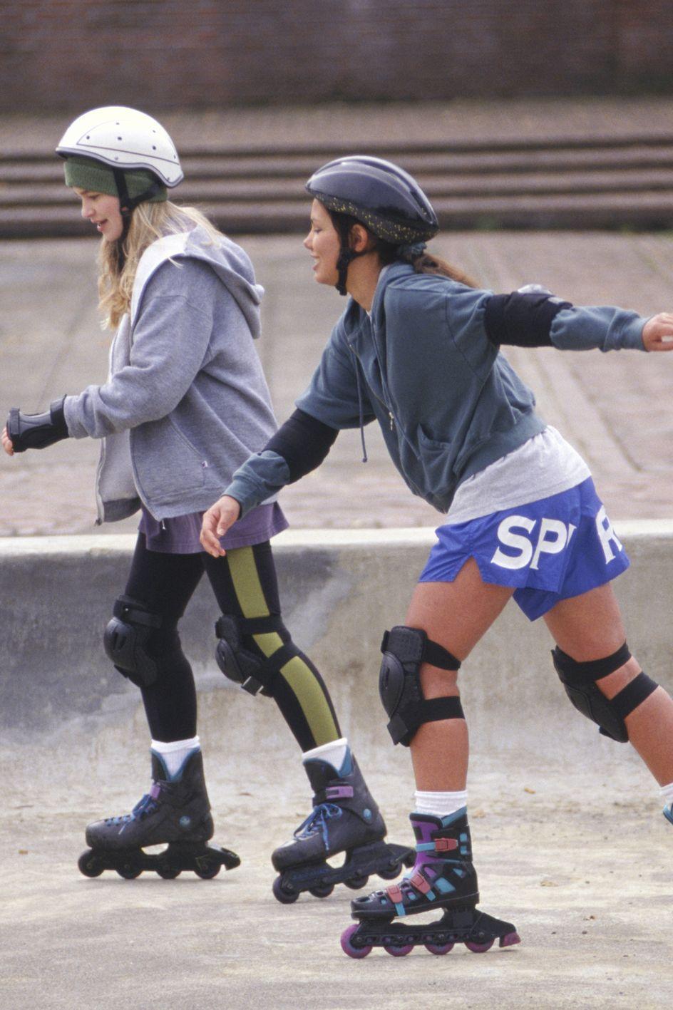 Two teenage girls (14-15) inline skating in park
