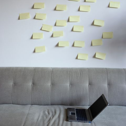 Laptop on chair, sticky notes on wall