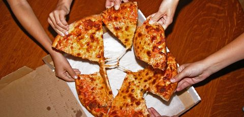 People grabbing slices of pizza, overhead view