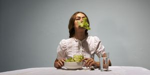 Woman sitting at table, eating lettuce