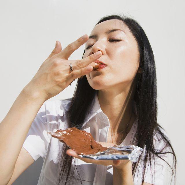 Woman eating melting chocolate, close-up