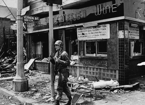 an armed national guard patrolman leans against a street sign, smoking a cigarette and standing in rubble following the watts riots, los angeles, california, august 1965 photo by hulton archivegetty images