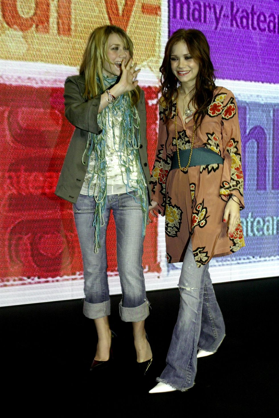 February 11, 2004 At the launch of their clothing line in Paris, the twins went for very different looks. Ashley wore a olive green blazer and blue jeans combo and Mary-Kate sported a belted dress over flared blue jeans.