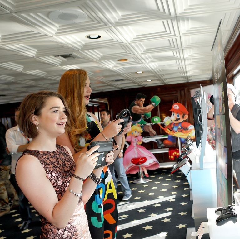 July 25, 2014 Maisie and Sophie play video games together at the Nintendo Lounge on the TV Guide Magazine Yacht at Comic-Con (are they playing a GoT game? Who's winning??).