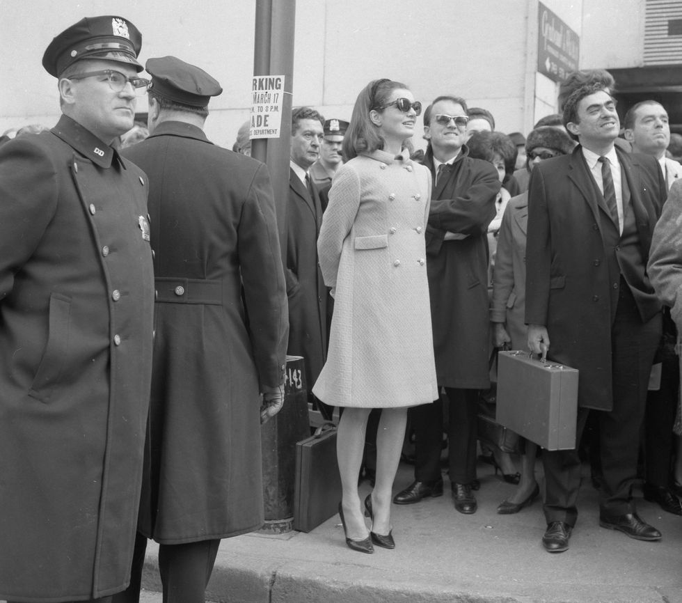Jacqueline Kennedy stands on tiptoes to watch the St. Patrick's Day parade at 57th Street in 1966.