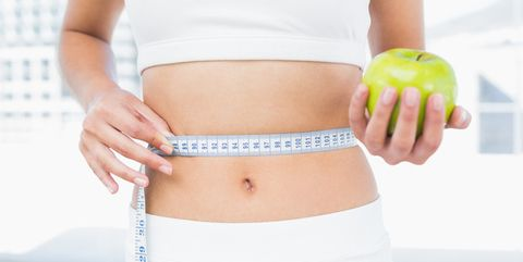 close up mid section of a young woman measuring waist as she holds apple in fitness studio