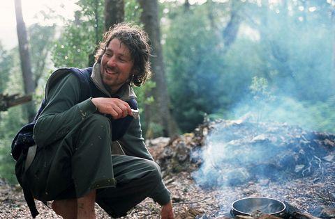 A trekker cooks dinner while camping inside the Tarkine, the