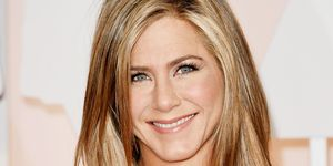 Jennifer Aniston smiles in a cream dress at the 87th Annual Academy Awards.
