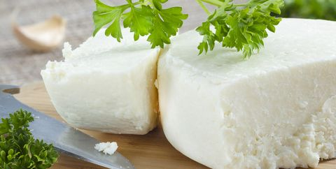 cotija cheese with cilantro on cutting board