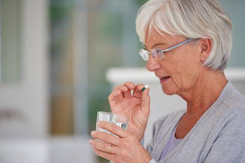 woman taking omeprazole capsule