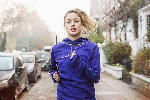 Female runner running down urban street.