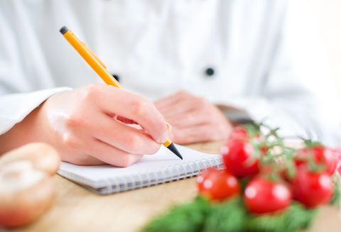 Close-up of chef writing in a notebook