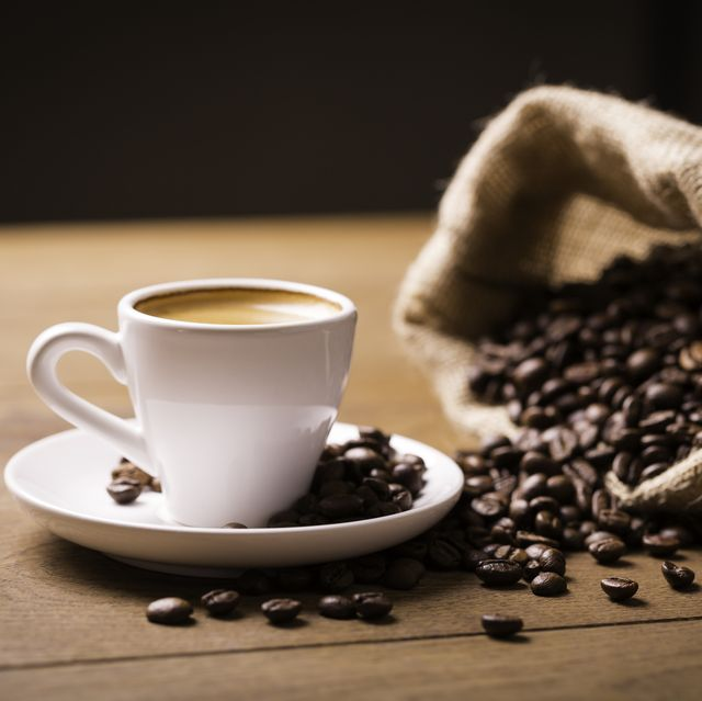 jute sack with coffee beans and espresso shot with crema on wooden table