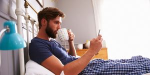 Man eating breakfast in bed while checking his smartphone