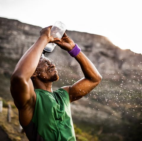 Athlete splashing water from his water bottle after a hard morning run