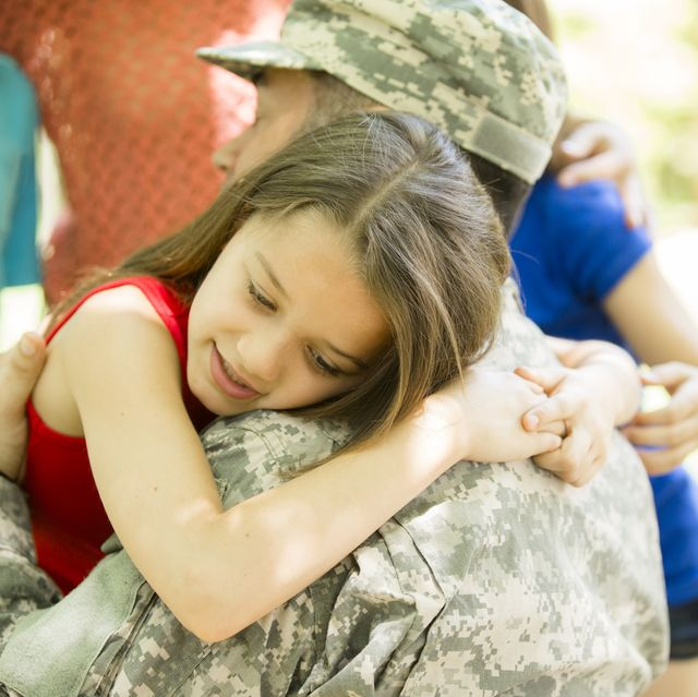 U.S. military veteran welcomed home by family. Children, hugs.