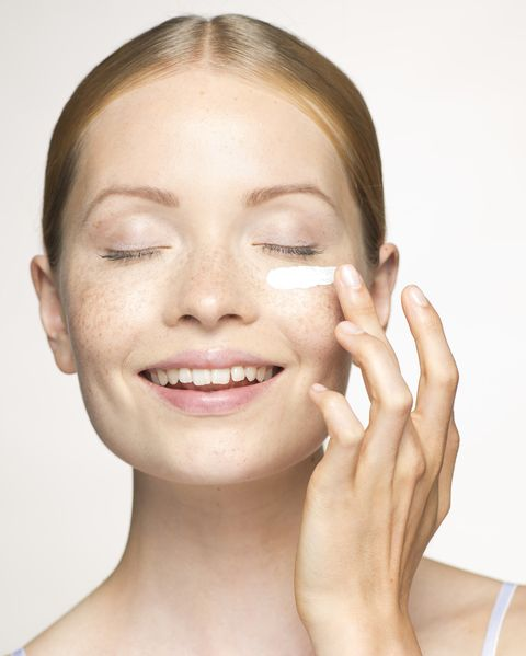 Young woman applying mositurizer under eye
