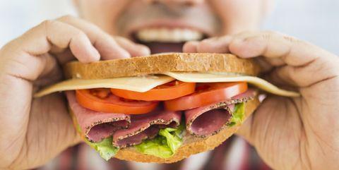 Mixed race man eating sandwich