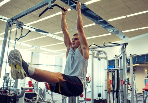 sport, fitness, lifestyle and people concept   young man flexing abdominal muscles on pull up bar in gym