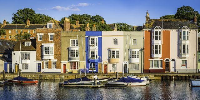colourful cottages and narrow higgledy piggledy homes reflecting in the tranquil harbour of a quaint fishing port under the blue summer skies of weymouth, dorset, uk prophoto rgb profile for maximum color fidelity and gamut