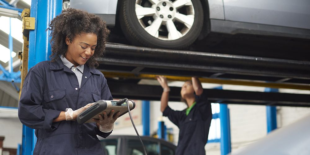 female garage mechanic conducting diagnostic check.