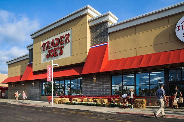 foxboro, massachusetts, usa   september 4, 2015 a steady flow of customers enter trader joes with empty hands and exit with overflowing bags and shopping carts with 457 stores, mostly in california, trader joes  is a market leader in organic and fresh food groceries in the united states  some locations, such as this one in foxboro, massachusetts also have a wide wine and beer selection