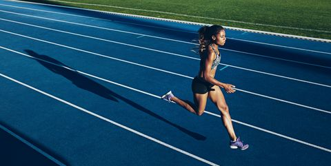 African woman running on racetrack