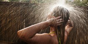 Mujer lavándose el pelo en una ducha externa.