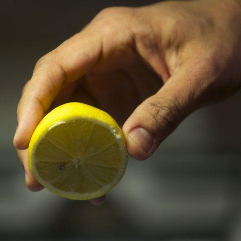 Man's hand squeezing lemon