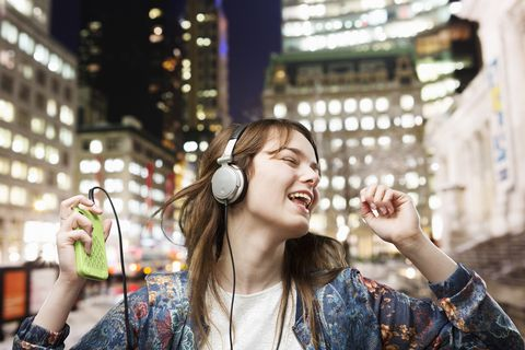 teenager dancing to music in city at night time