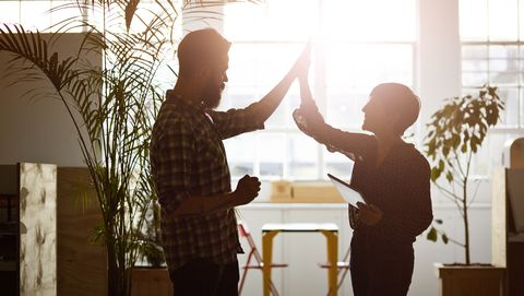 creative coworkers doing high five at the office, in the sunset