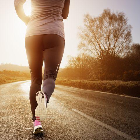 Female runner running along road