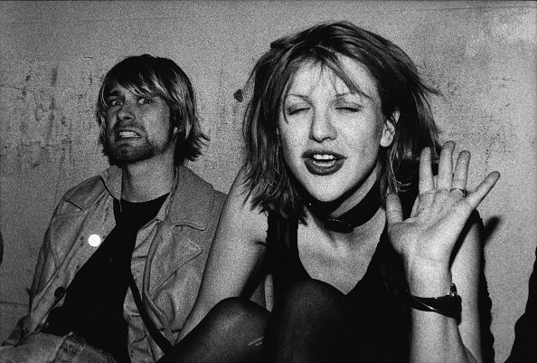 Kurt Cobain and Courtney Love pose for photograph, Kurt grimacing for the camera and Courtney waving, on VIP balcony during Mudhoney concert at the Hollywood Palladium in December 1992.
