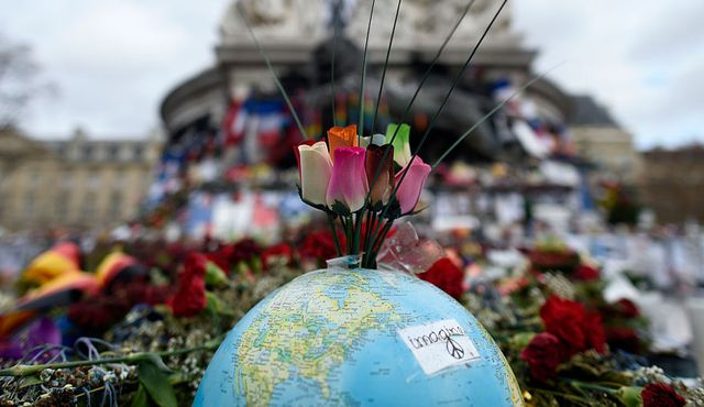 topshot   this picture taken on december 24, 2015 shows a globe and roses on a makeshift memorial at place de la republique in paris on december 24, 2015 to pay tribute to the victims of the november 13 terror attacks a coordinated series of gun and bomb attacks at several sites in paris on november 13 left 130 dead  afp  miguel medina        photo credit should read miguel medinaafp via getty images