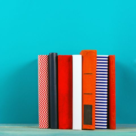 Row of colorful hardback books, open book on blue background