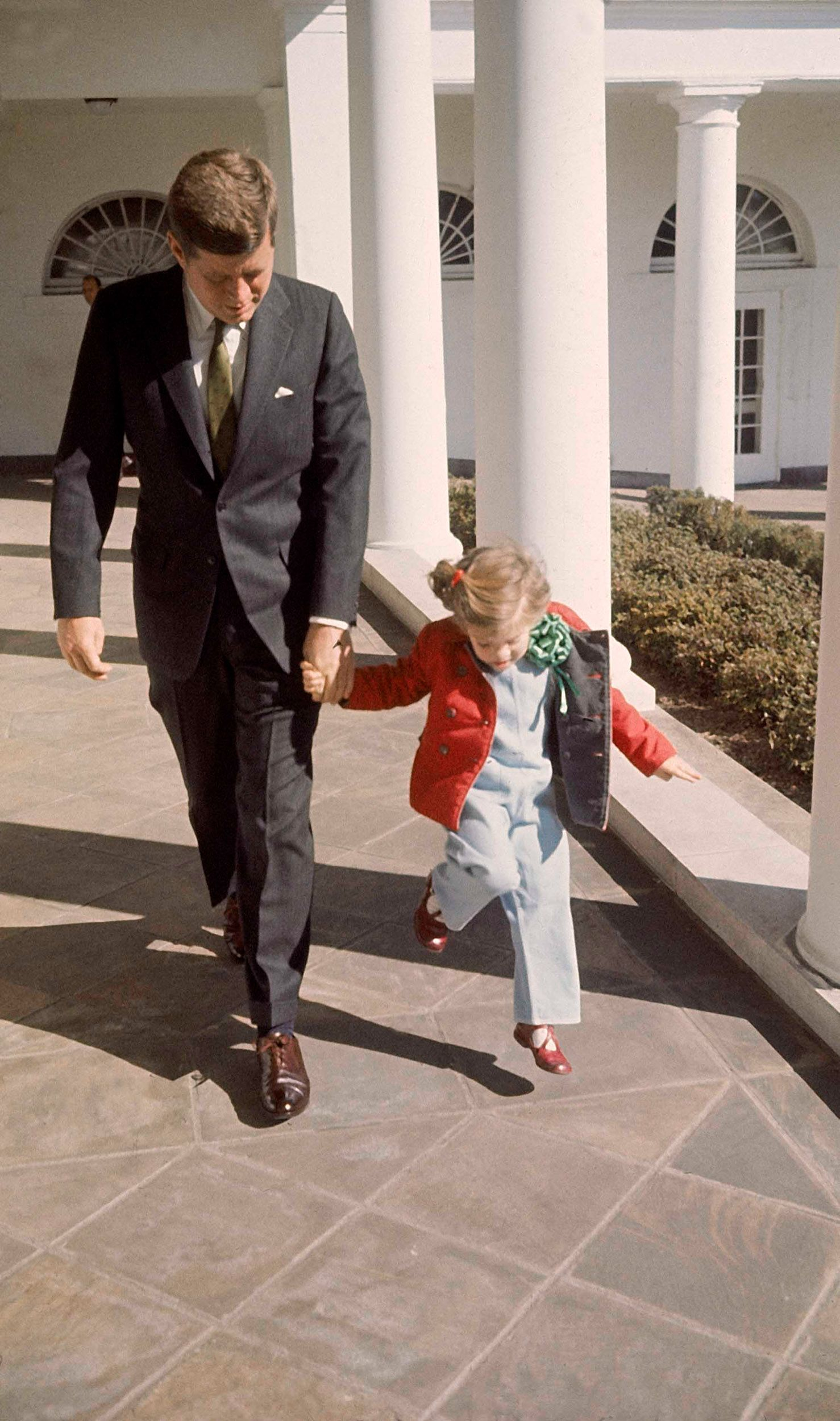President John F. Kennedy walking hand-in-hand with his daughter Caroline on St. Patrick's Day at the White House in 1961.