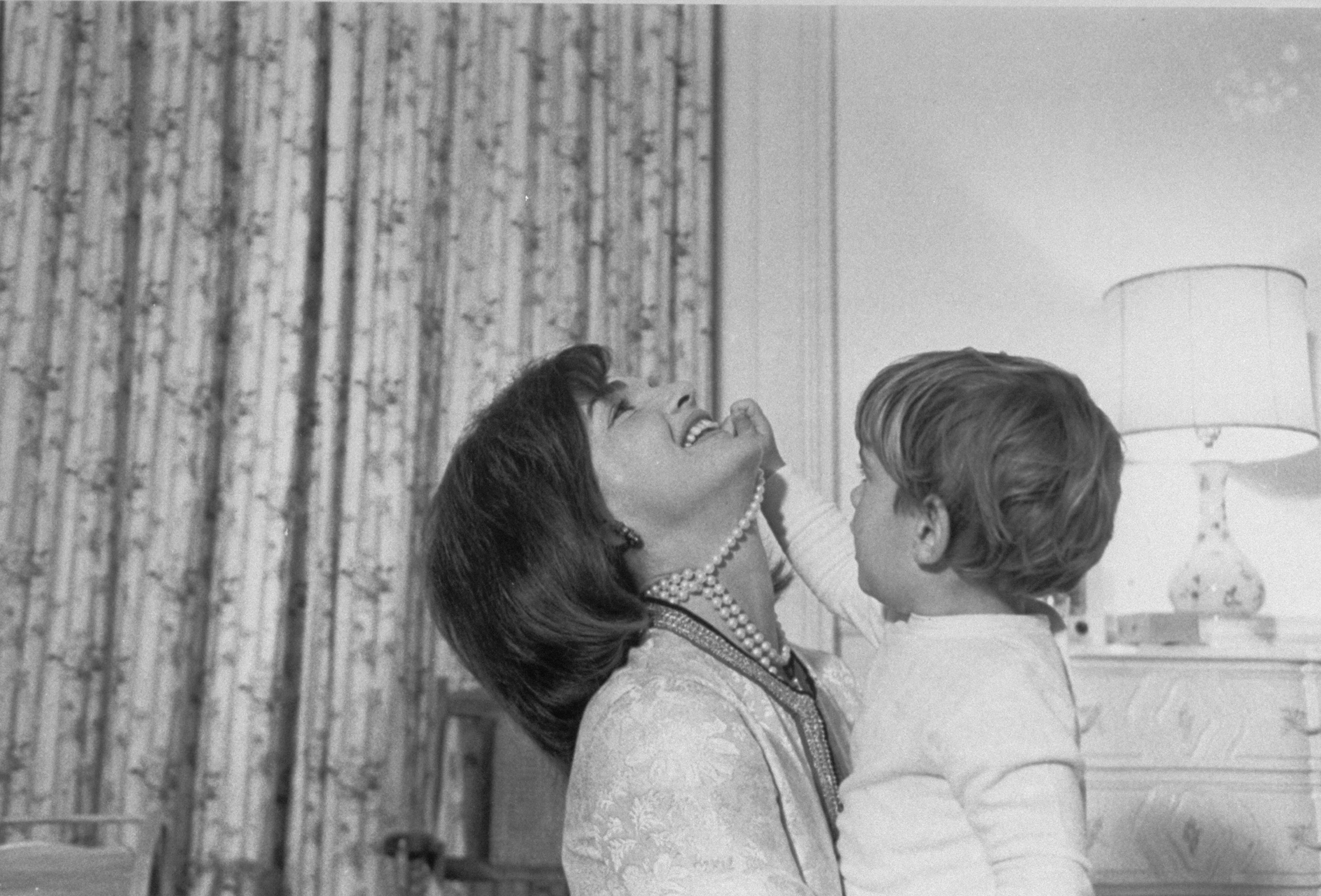 John F. Kennedy Jr. is seen playing with his mother's pearls.