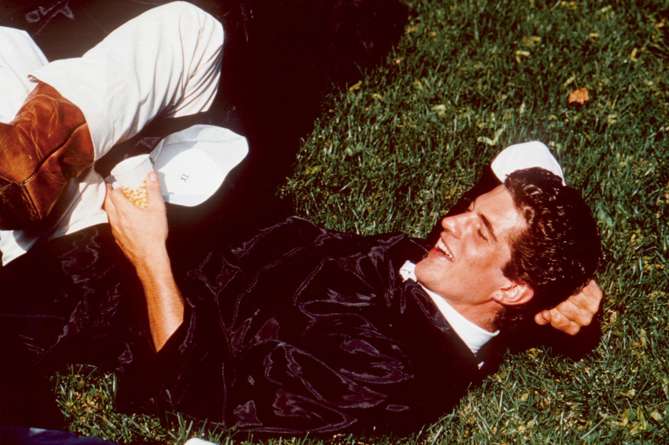 John F. Kennedy Jr. lies on the the grass in his robe at his graduation from Brown University, Rhode Island on June 6, 1983.