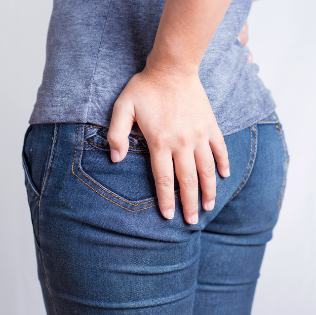 woman holding butt in pain