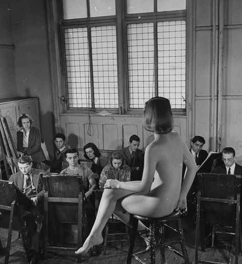 Nude female model posing before a class