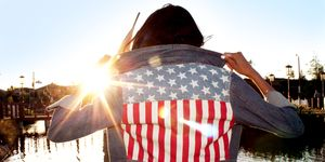 Girl With American Flag Jacket With Sunset