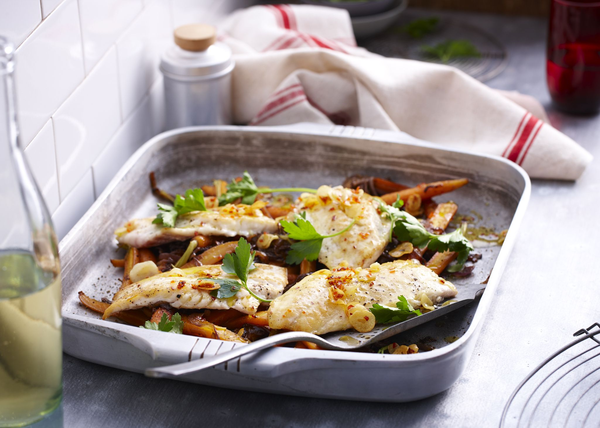 Baking tin with roast snapper with herb garnish