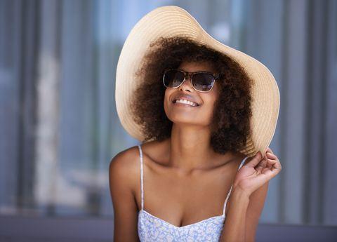 shot of a woman wearing a sun hat relaxing outside