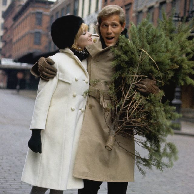 george segal and maggie london walk down a city street, their arms wrapped around each other, he carries a small christmas tree she wears a white wool coat by dani jrs, black and white muffler by einier accessories, black bubble hat by veaumont, black gloves by hansen, and grey stockings by berkshire he wears a khaki trench coat with slacks photo bylouis faurercondé nast via getty images