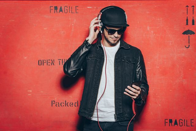 handsome young man adjusting his headphones and looking at his smart phone while standing against red background